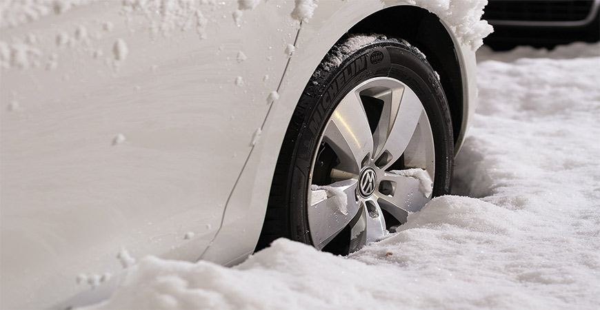 Close up of car tire stuck in snow