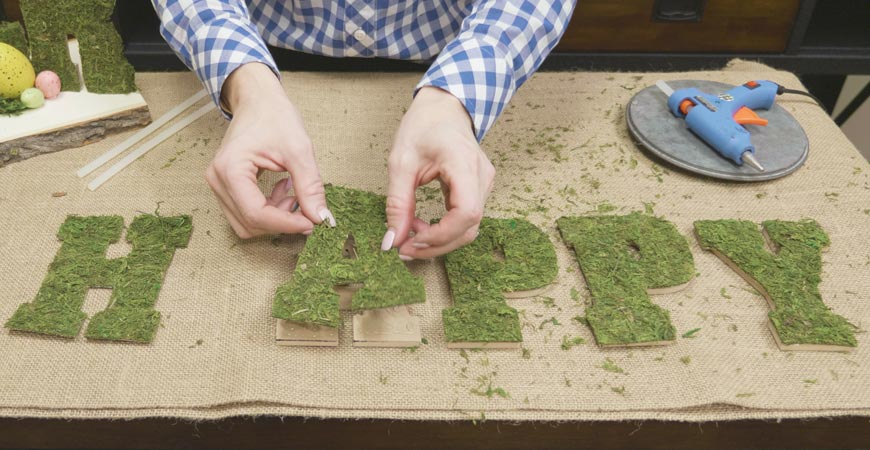 Glue moss onto each wooden letter