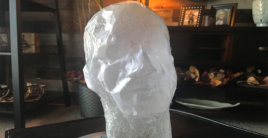 Remove mannequin head from tape.