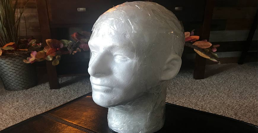 Wrap packing tape around mannequin head.